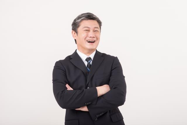 腕くみしながら笑う中年男性