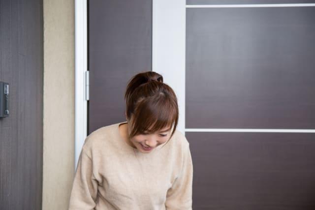玄関で挨拶する女性