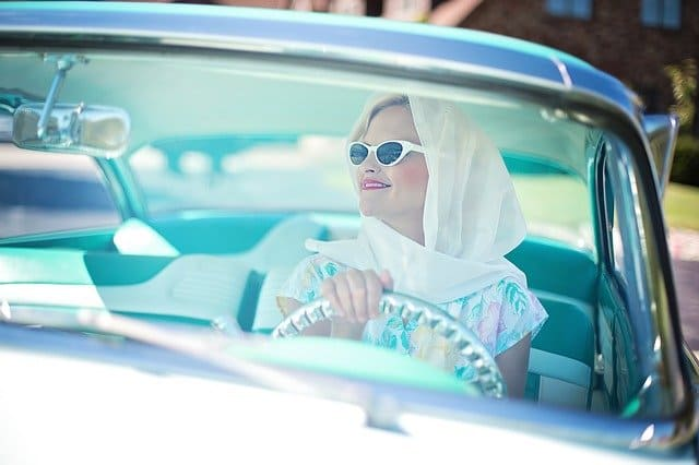クラシックカーを運転する女性
